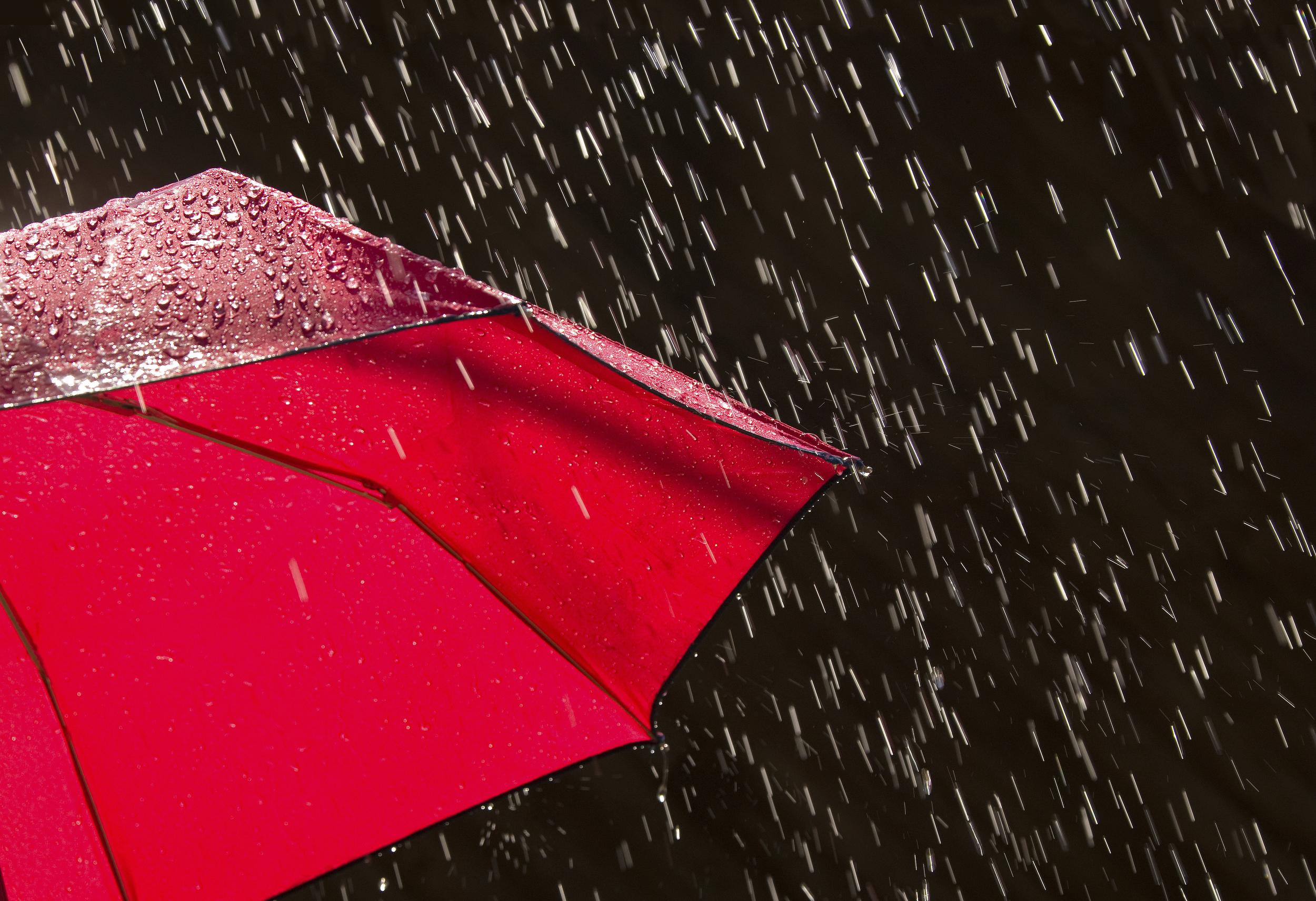 Red umbrella facing pelting rain.