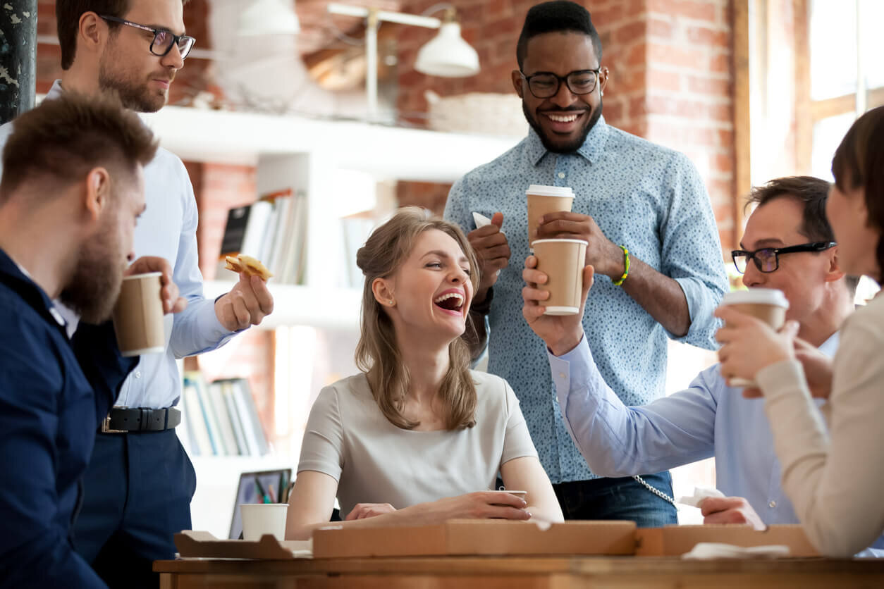 Office team laughing and drinking coffee and eating pizza together in the office breakroom.