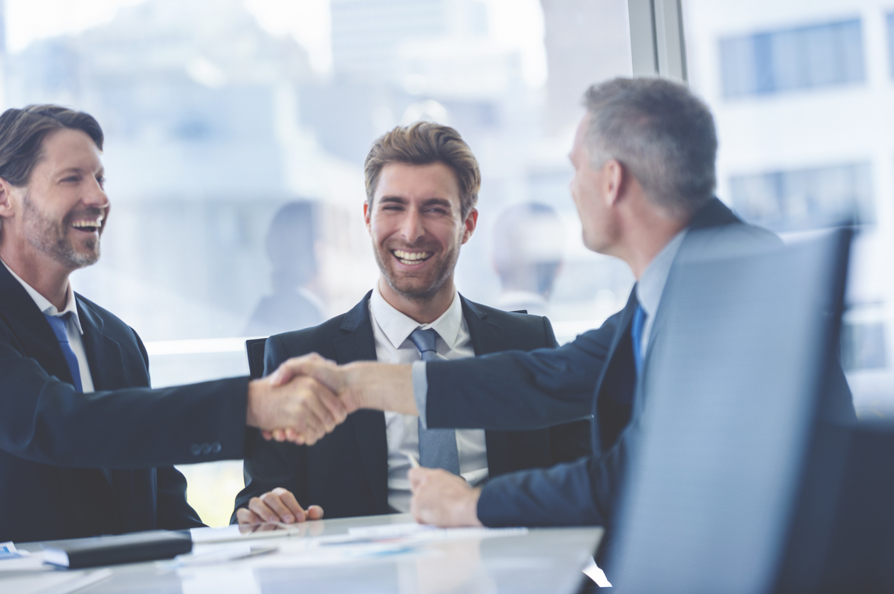 Group of businessman smiling and shaking hands over table in office environment.