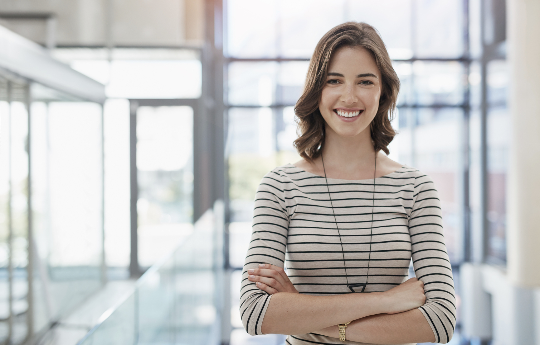Young smiling businesswoman standing with arms crossed at the office.