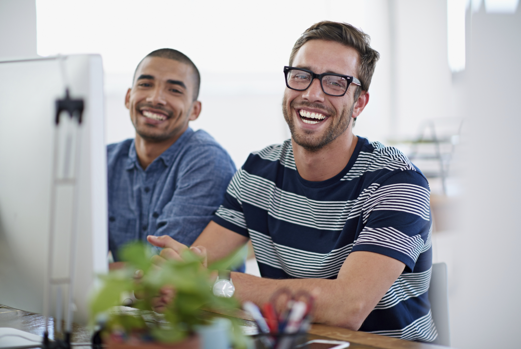Two casually dressed young bearded men sitting at desk smiling at the camera. The have large desktop computers in front of them.