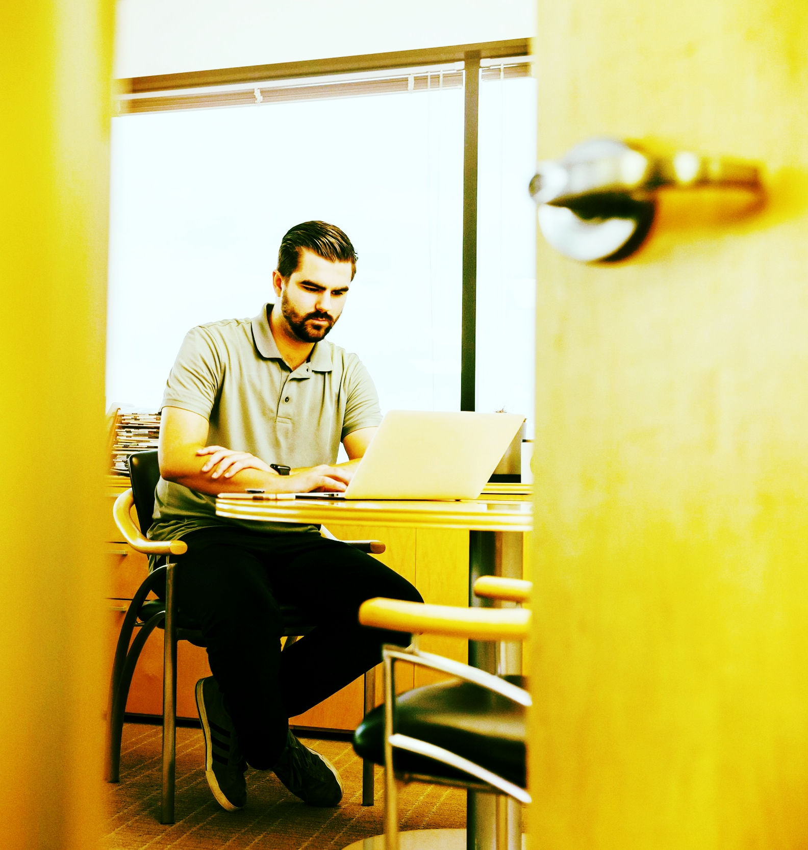 A casually dressed bearded white man sits at a small table where he works on his laptop.