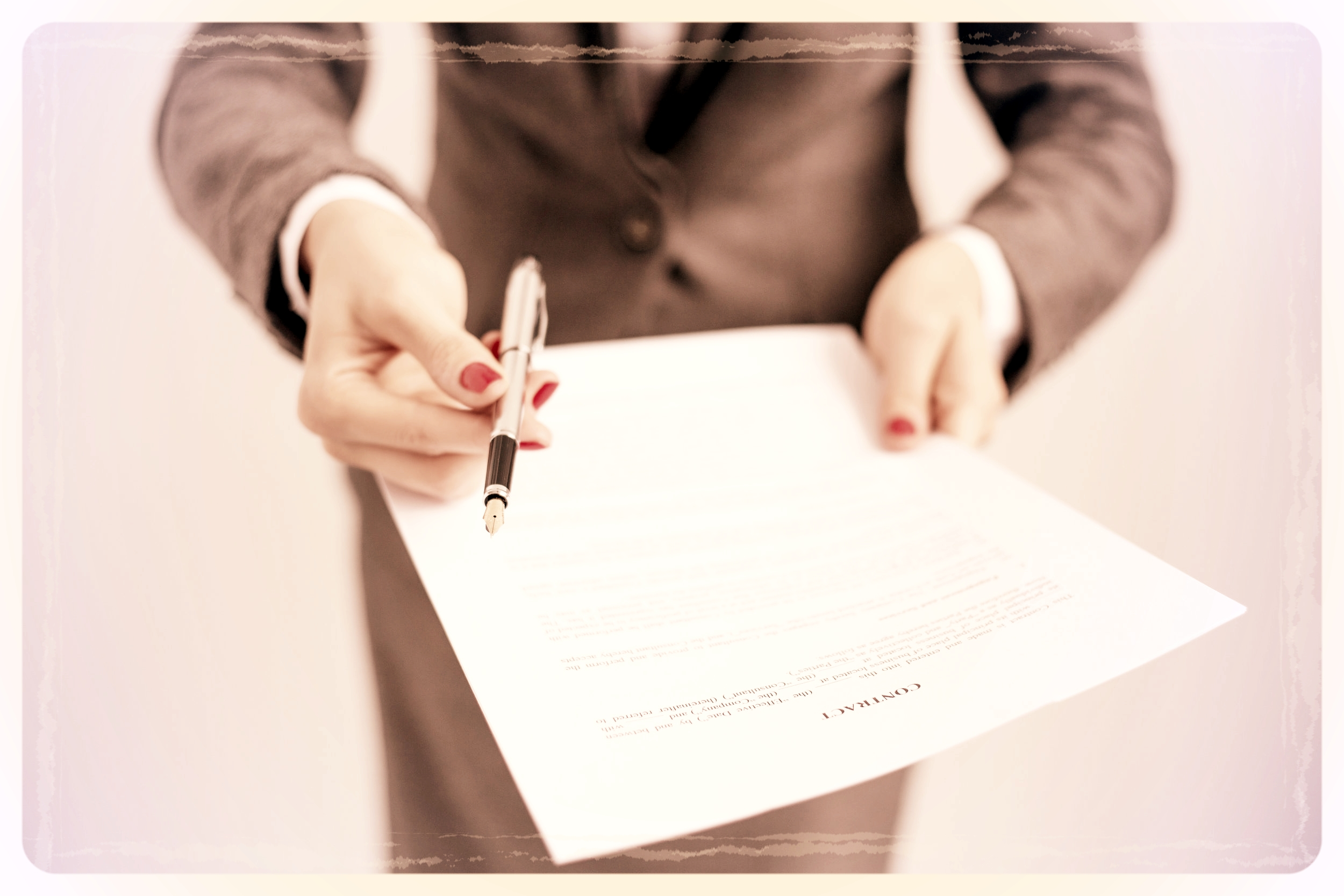In sepia tones, a woman in a business suit hands a contract to the camera. She holds a fancy fountain pen in her hand and offers it with the contract.