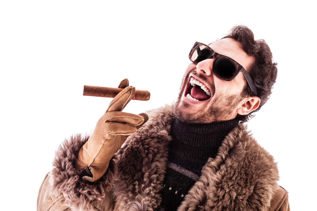 A bearded white man wears sunglasses, a fancy fur coat with leather gloves. He is holding an unlit cigar his right hand fingers and he is smiling in a laughing way. He is leaning back a bit.