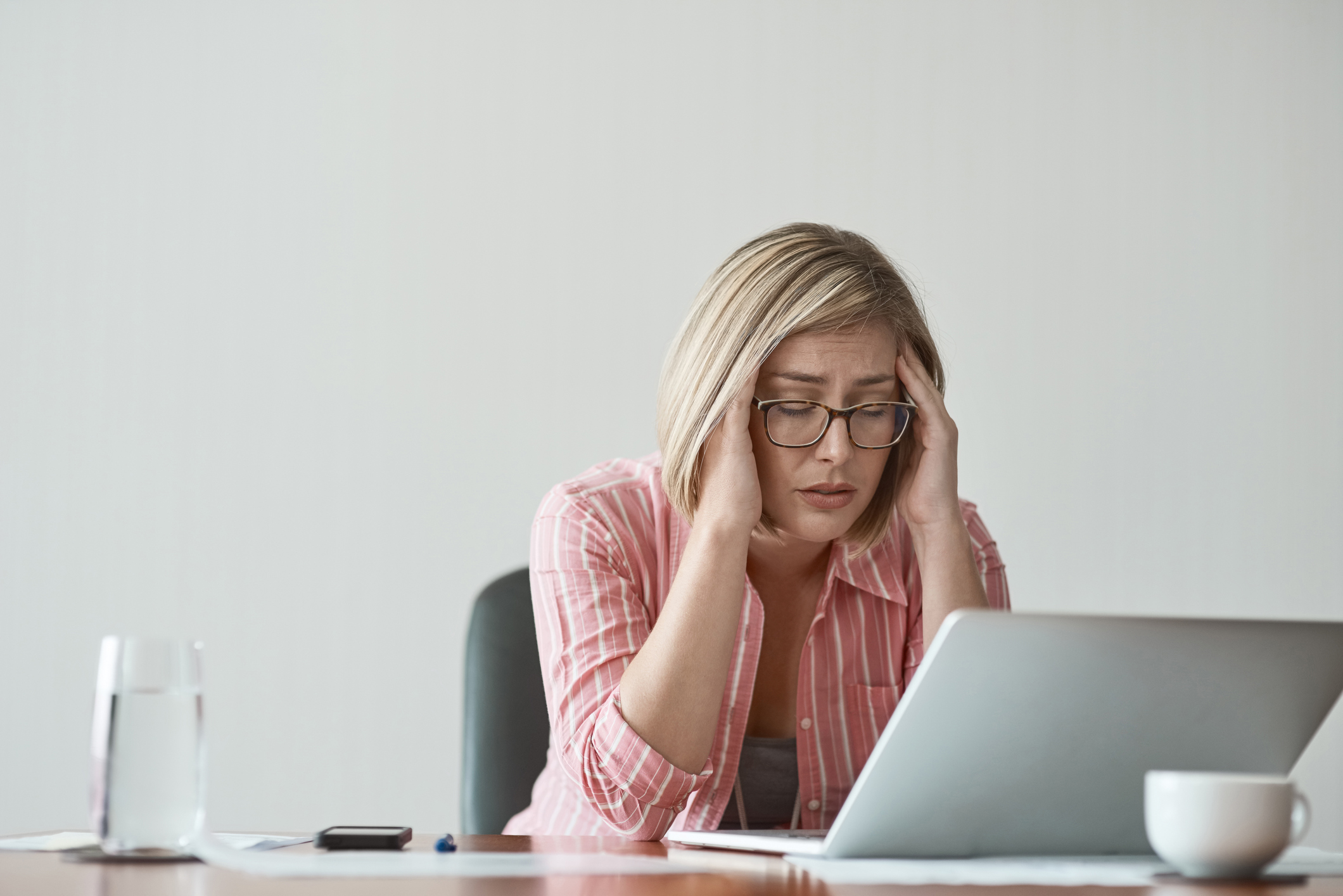 A woman appears to be stressed out as she works in front of her laptop. She is rubbing her temples and has her eyes closed.