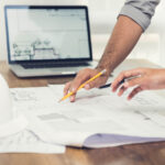 Two people work on a set of plans for a building or an office suite.
