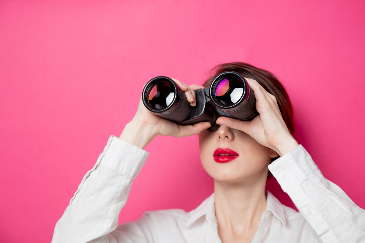 A women looks through binoculars at a scene that is off camera.