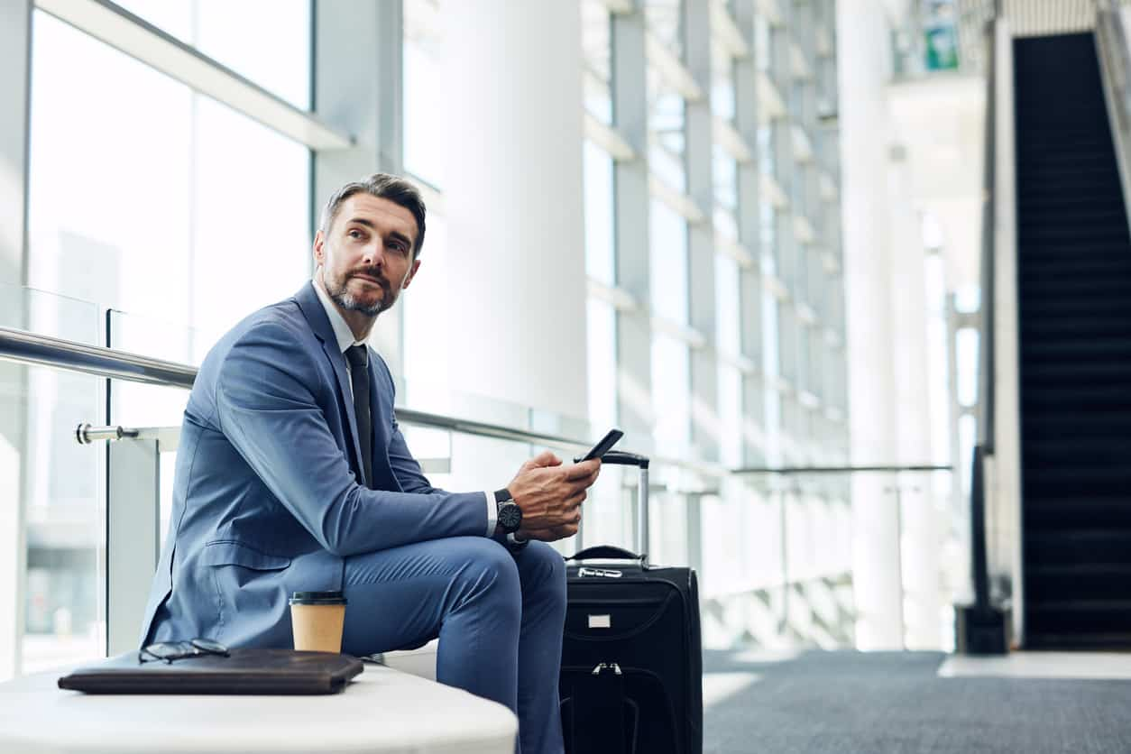 An older man in a suit is sitting down looking at someone or something that is off camera. He has a cup of coffee and small suitcase next to him. He holds a phone in his hand.