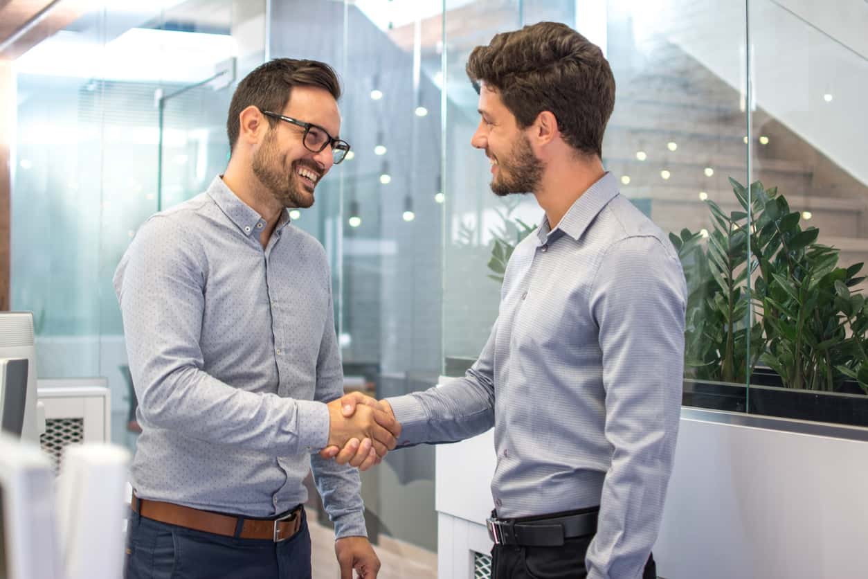 Two mean in business casual attire shake hands. They appear to be in an office and they are smiling and happy.