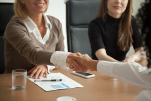Three women in a conference room. Two of the women are reaching across the table to shake hands.