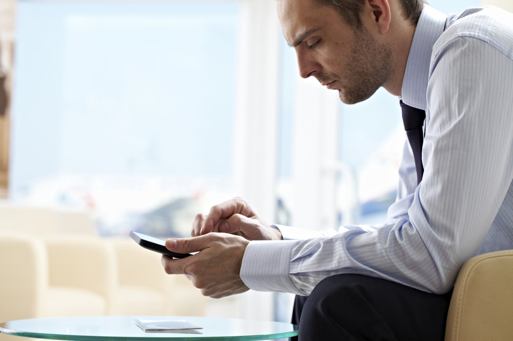 A business person sitting in his chair looking at his phone.