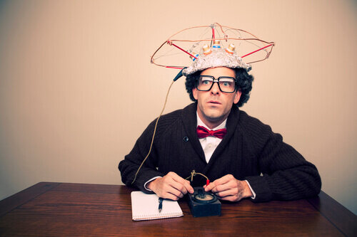 A man sits at a desk with a blank note pad and a pen. He has thick glasses and a red bow tie. He is wearing a strange contraption on his his head that appears to be made out tinfoil and wires. There is a large wire extending out of the head devise that connects to a hand held control that the man appears to be operating. The man has a bewildered distant expression on his face.