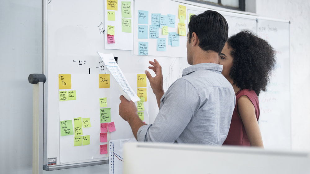 A man and woman standing at a whiteboard applying sticky notes and discussing their business goals.
