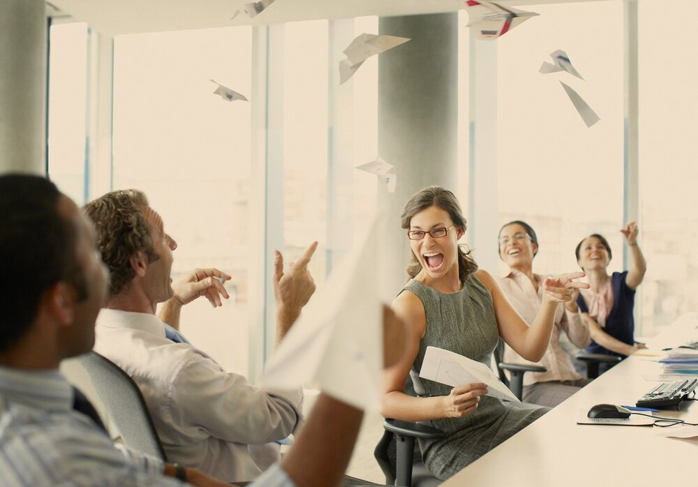 Salespeople having fun at the office laughing and flying paper airplanes. Woman with big smile and red-brown glasses laughing.