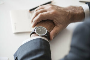 Man looking at his watch noticing time is passing.