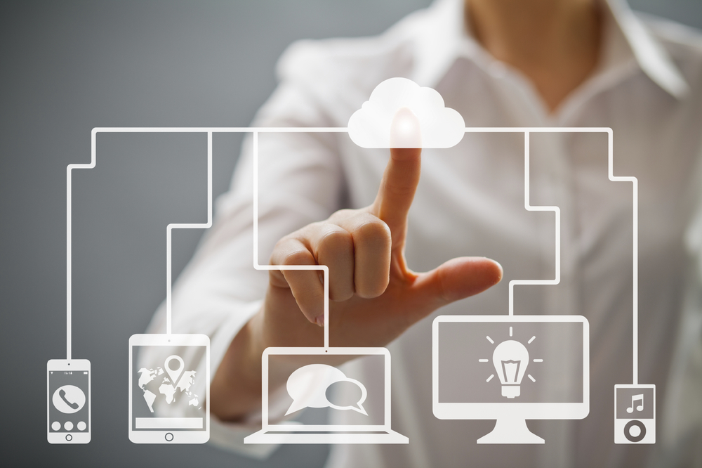 Woman pointing to screen with cloud, mobile phone and computer graphic.