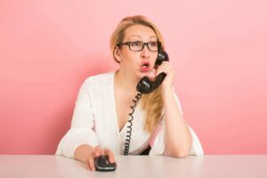 Woman with glasses on a phone with a mouse with a pink background.