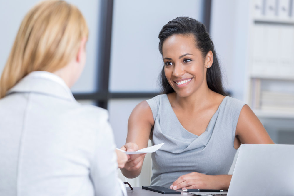 Woman giving an interview and smiling at another woman at the office while sitting at a desk.