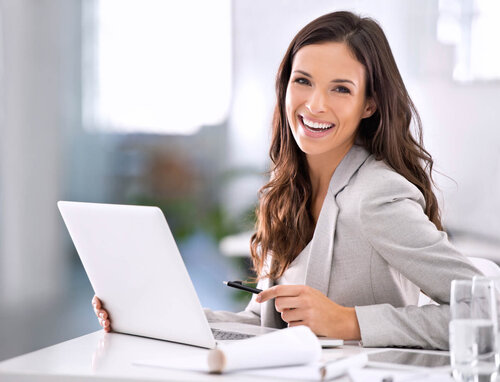 Young woman sales recruiter in formal business attire smiling with her laptop and water at software sales recruiting firm Optimal Sales Search.