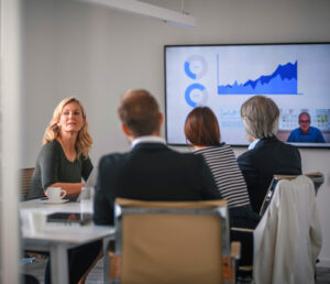 People sitting in a conference room with a big screen showing data.